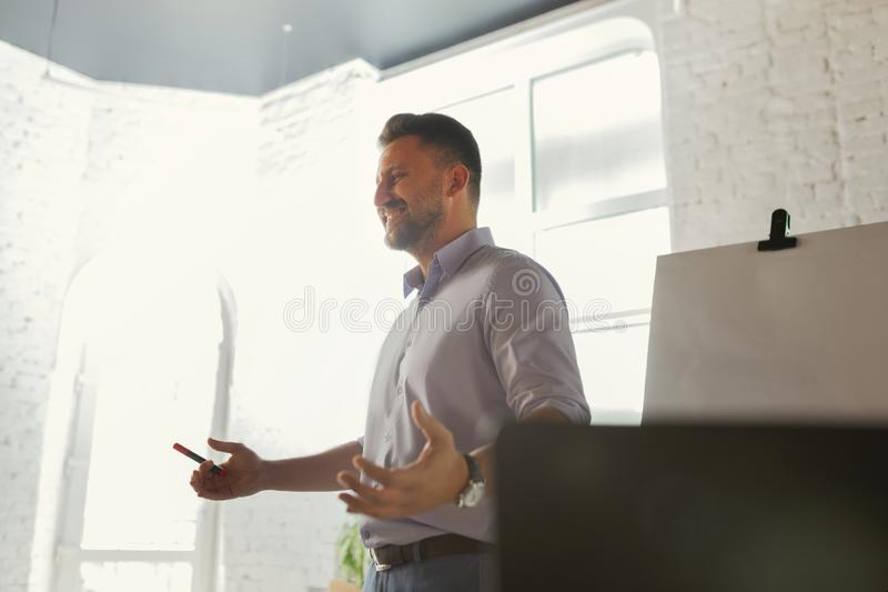 Male speaker giving presentation in hall at university workshop stock image