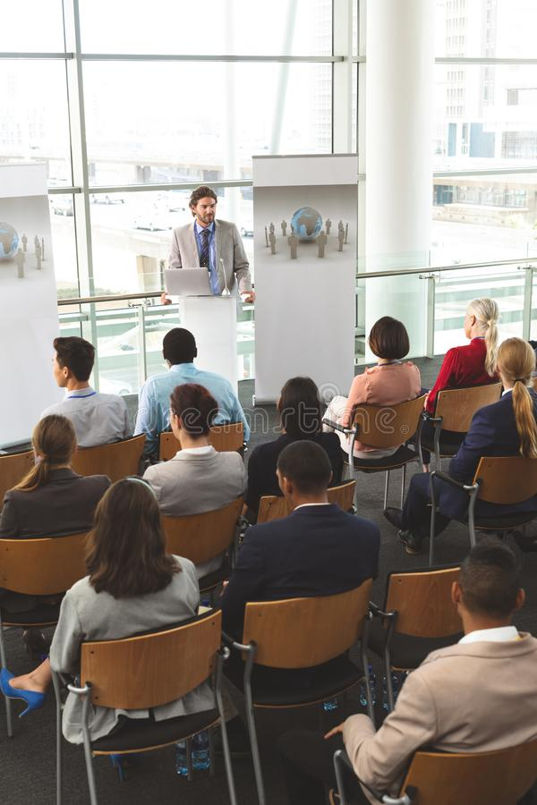 Male speaker with laptop speaks in a business seminar royalty free stock images