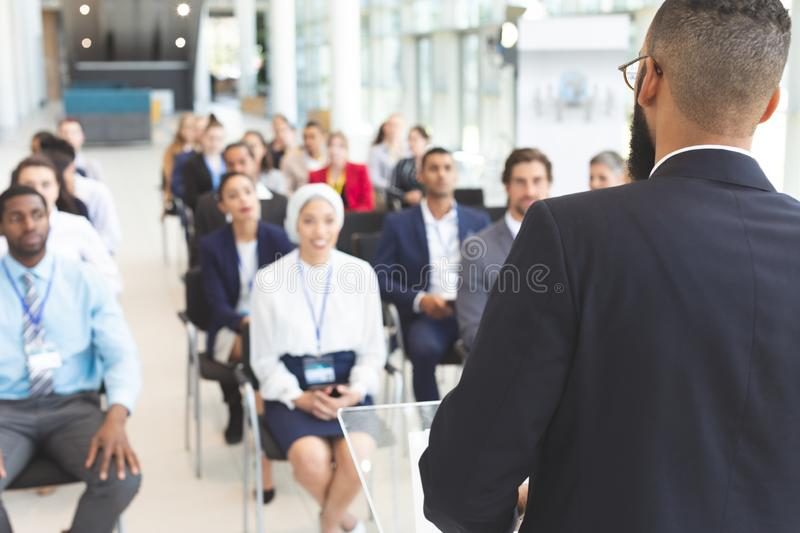 Male speaker speaks in a business seminar. Rear view of mixed race male speaker speaks to diverse business people in a business seminar in a conference room royalty free stock photos