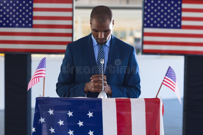 Male speaker standing with hands clasped at podium table. Front view of Male speaker standing with hands clasped at podium table in business seminar stock photos