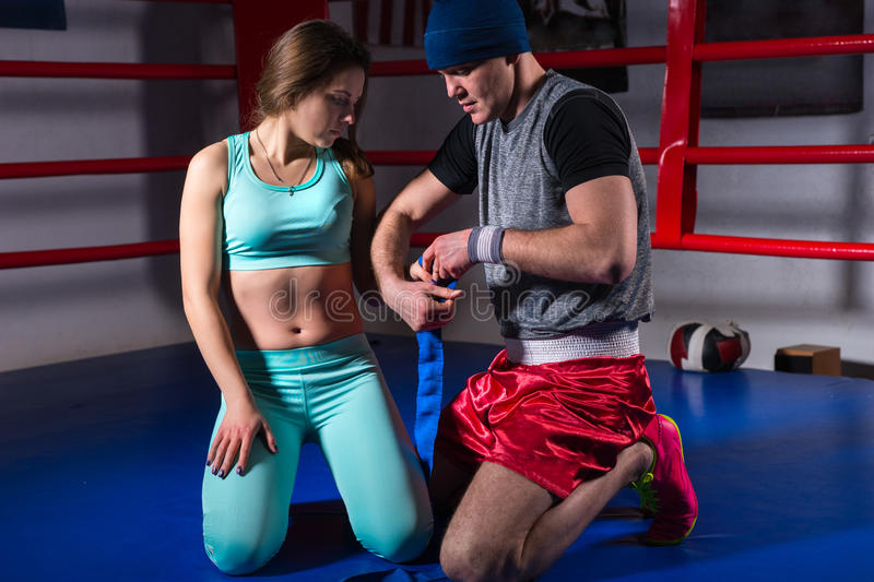 Male sporty boxer preparing bandages for young female royalty free stock photo