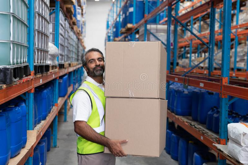 Male staff carrying cardboard boxes in warehouse stock image
