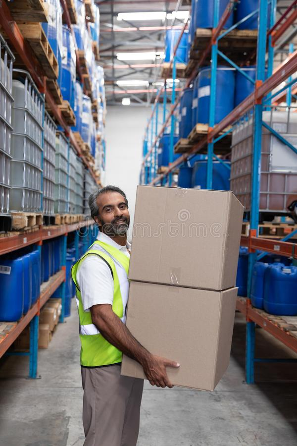 Male staff carrying cardboard boxes in warehouse stock photography