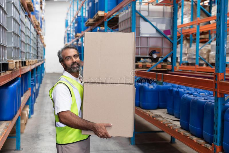 Male staff carrying cardboard boxes in warehouse stock photos