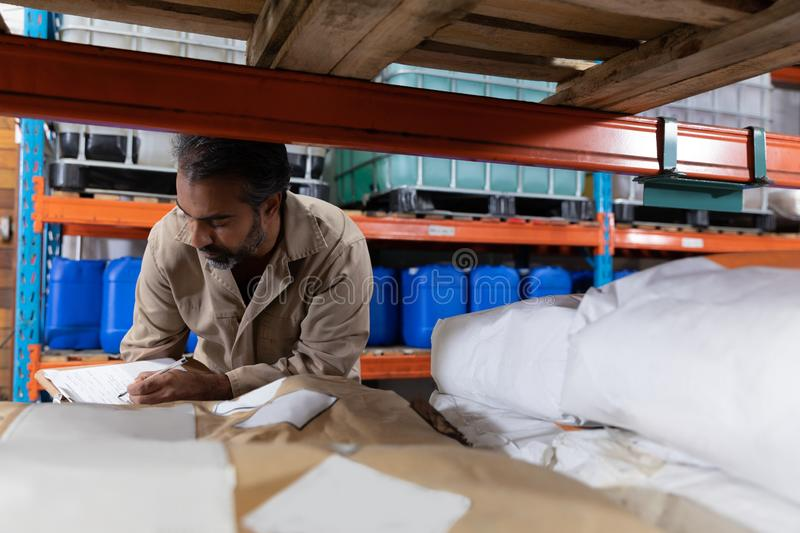 Male staff checking stocks in warehouse. Asian male staff checking stocks in warehouse. This is a freight transportation and distribution warehouse. Industrial royalty free stock images