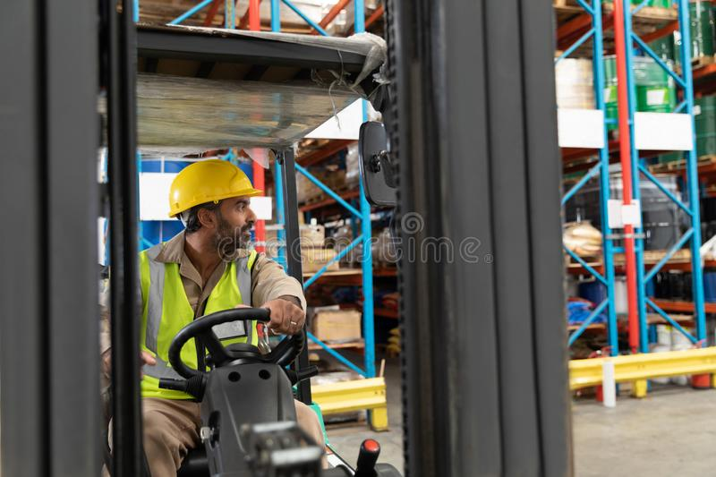 Male staff driving forklift in warehouse. Asian male staff driving forklift in warehouse. This is a freight transportation and distribution warehouse. Industrial royalty free stock photo