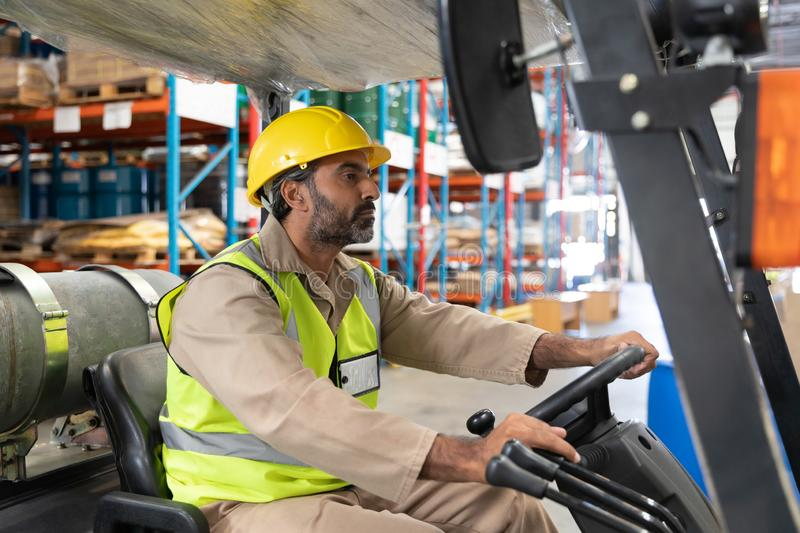 Male staff driving forklift in warehouse. Asian male staff driving forklift in warehouse. This is a freight transportation and distribution warehouse. Industrial stock image