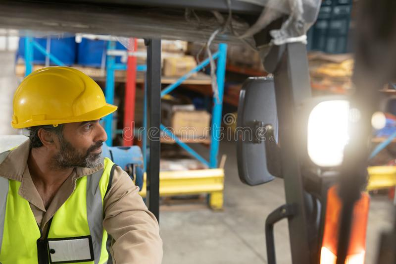 Male staff driving forklift in warehouse. Asian male staff driving forklift in warehouse. This is a freight transportation and distribution warehouse. Industrial stock photography