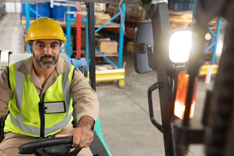 Male staff driving forklift in warehouse. Asian male staff driving forklift in warehouse. This is a freight transportation and distribution warehouse. Industrial stock photos