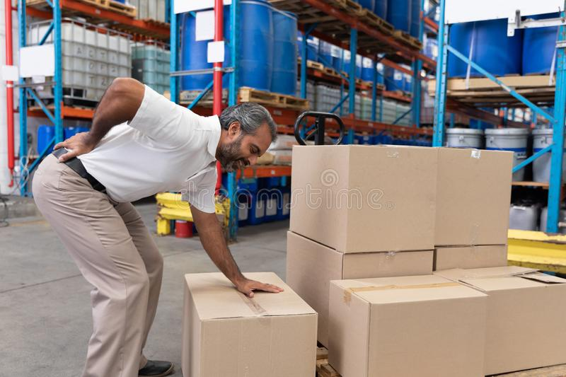 Male staff suffering from back pain while holding heavy cardboard box royalty free stock photos