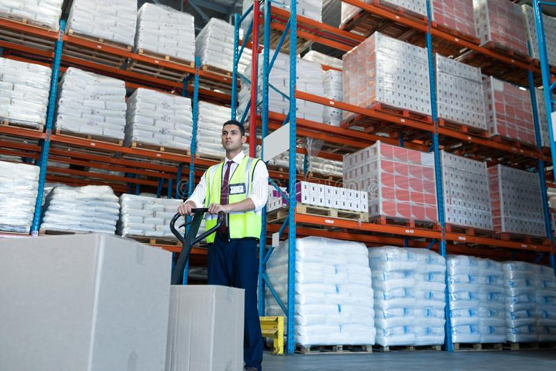 Male staff using pallet jack in warehouse. Low angle view of Caucasian male staff using pallet jack in warehouse. This is a freight transportation and royalty free stock image