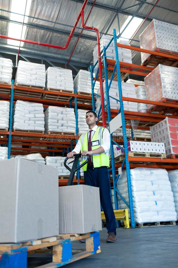 Male staff using pallet jack in warehouse. Low angle view of Caucasian male staff using pallet jack in warehouse. This is a freight transportation and royalty free stock photos