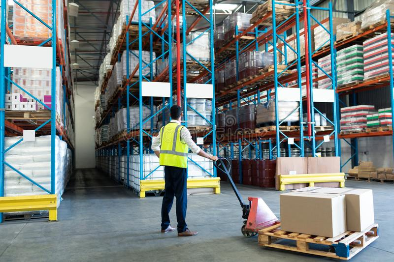 Male staff using pallet jack in warehouse. Rear view of Caucasian male staff using pallet jack in warehouse. This is a freight transportation and distribution royalty free stock image