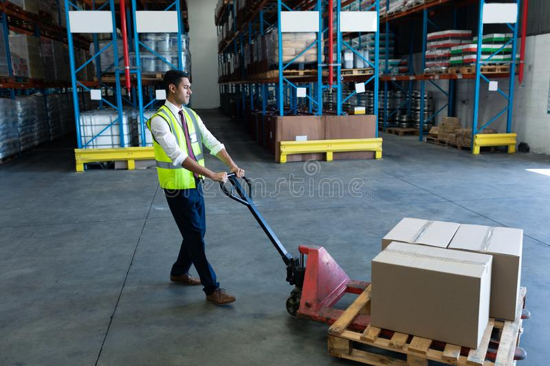 Male staff using pallet jack in warehouse. Side view of Caucasian male staff using pallet jack in warehouse. This is a freight transportation and distribution royalty free stock image