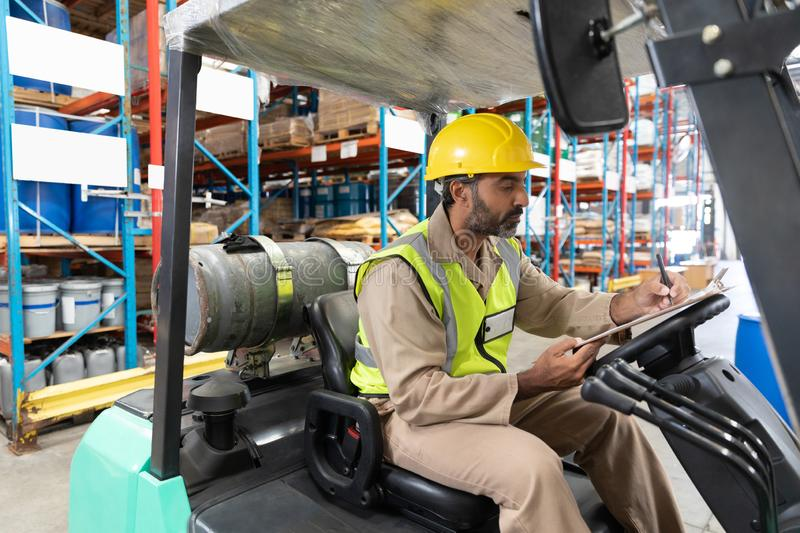 Male staff writing on clipboard while sitting on forklift in warehouse. Asian male staff writing on clipboard while sitting on forklift in warehouse. This is a royalty free stock photos