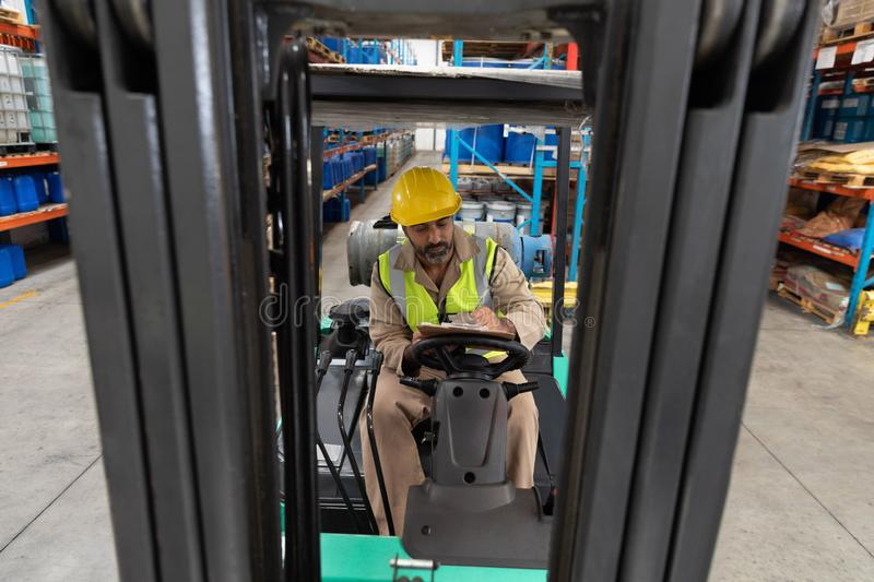 Male staff writing on clipboard while sitting on forklift in warehouse. Asian male staff writing on clipboard while sitting on forklift in warehouse. This is a royalty free stock images