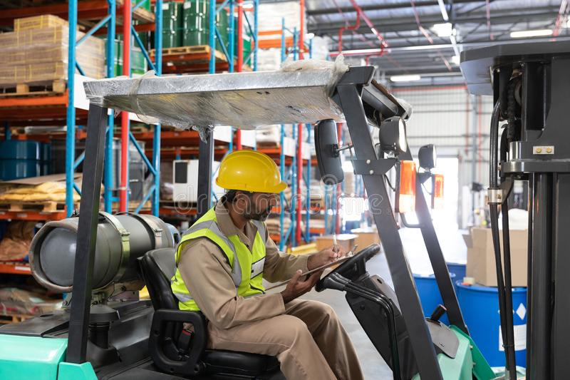 Male staff writing on clipboard while sitting on forklift in warehouse. Asian male staff writing on clipboard while sitting on forklift in warehouse. This is a stock photos