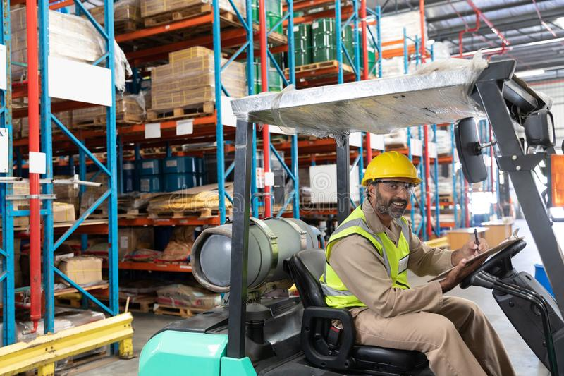 Male staff writing on clipboard while sitting on forklift in warehouse. Portrait of male staff writing on clipboard while sitting on forklift in warehouse. This royalty free stock photo