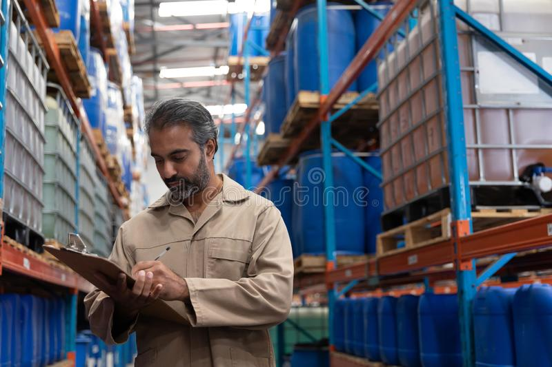 Male staff writing on clipboard while standing in warehouse. Asian male staff writing on clipboard while standing in warehouse. This is a freight transportation royalty free stock photos