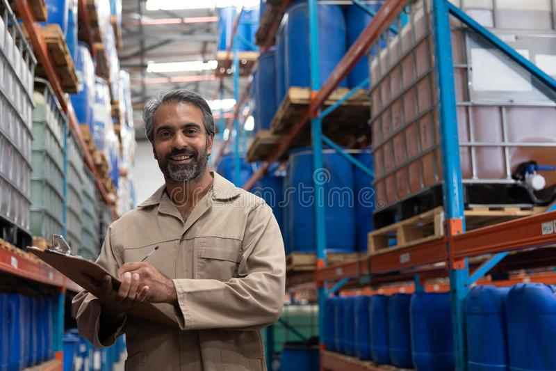 Male staff writing on clipboard standing in warehouse. Portrait of male staff writing on clipboard standing in warehouse. This is a freight transportation and stock image