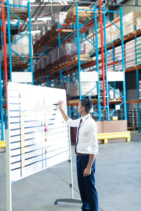 Male staff writing on sticky notes in warehouse. Side view of handsome young Caucasian male staff  writing on sticky notes in warehouse. This is a freight stock image