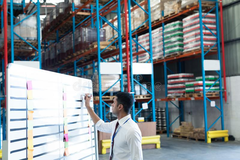 Male staff writing on whiteboard in warehouse. Side view of young handsome Caucasian male staff writing on whiteboard in warehouse. This is a freight stock photos