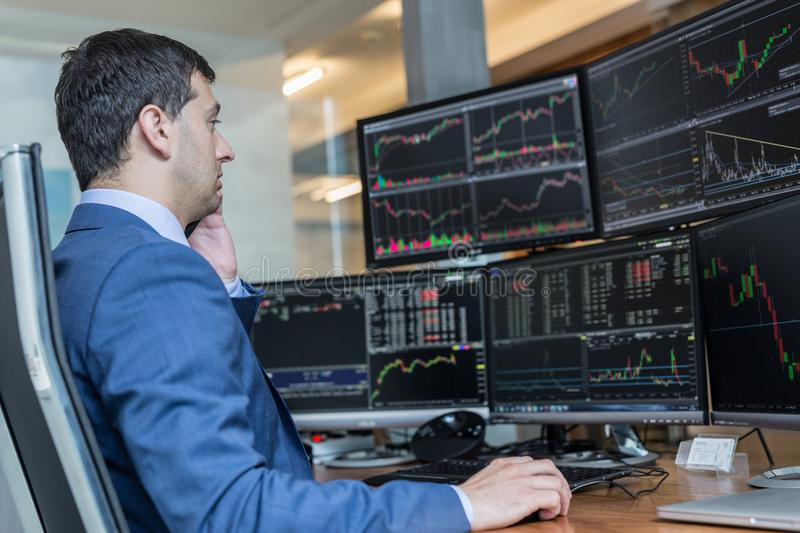 Stock broker trading online watching charts and data analyses on multiple computer screens. Male stock broker trading online watching charts and data analyses royalty free stock images