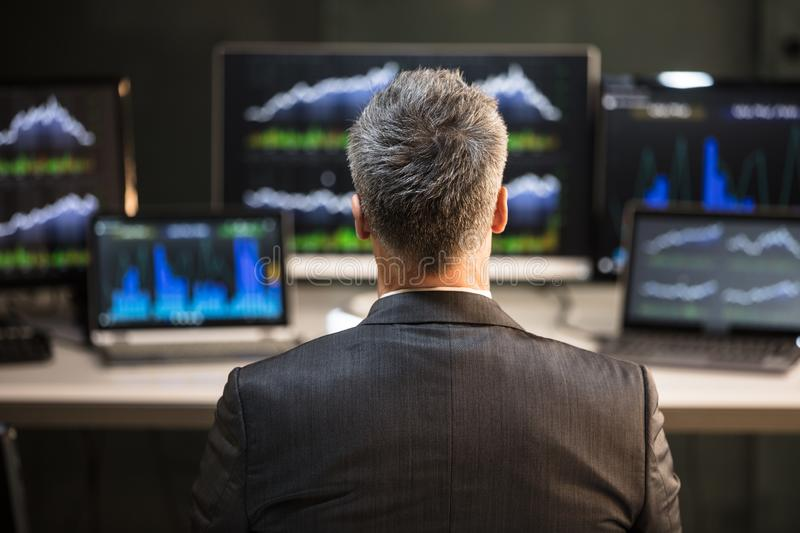 Rear View Of A Male Stock Market Broker. Male Stock Market Broker Looking At Computer And Laptop Showing Graph On Screen stock images