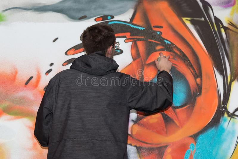 Male street artist: spraying on public urban city wall stock image