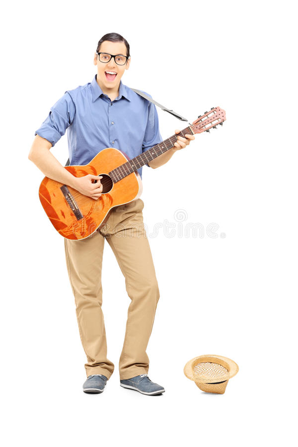 Male street musician playing guitar collecting money in hat royalty free stock photo
