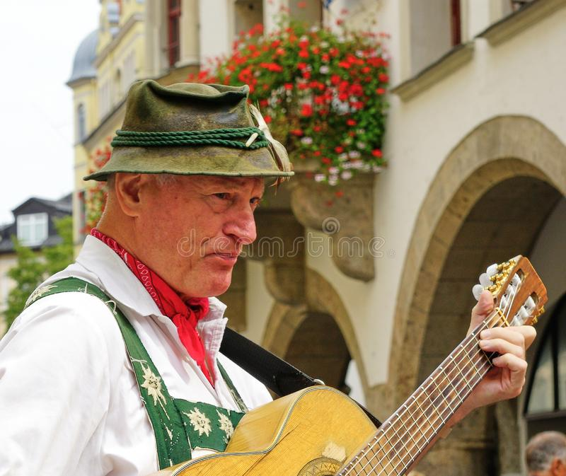 Male Street Performer in Traditional Bavarian Clothing. Close up of senior male street performer in old town Munich, playing guitar and dressed in traditional royalty free stock photo