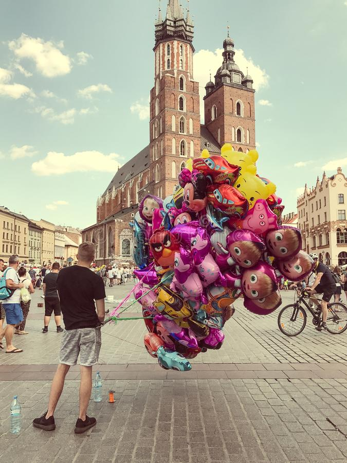 Male street vendor sells colorful popular cartoon character heli. Krakow, Poland - July 29, 2017 : Male street vendor sells colorful popular cartoon character stock photos