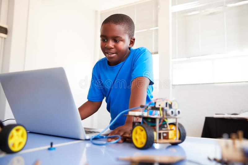 Male Student Building And Programing Robot Vehicle In After School Computer Coding Class royalty free stock images