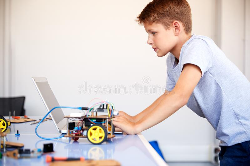 Male Student Building And Programing Robot Vehicle In School Computer Coding Class royalty free stock images