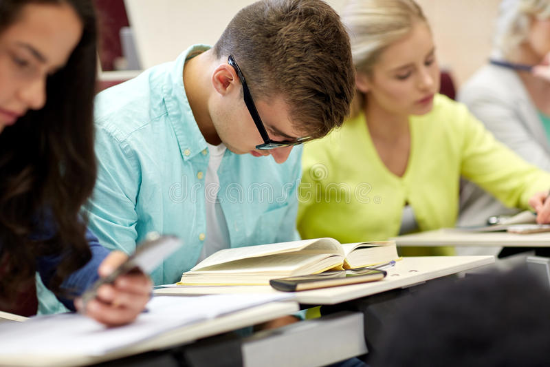 Male student in glasses reading book at lecture. Education, high school, university, learning and people concept - male student in glasses reading book at royalty free stock photo