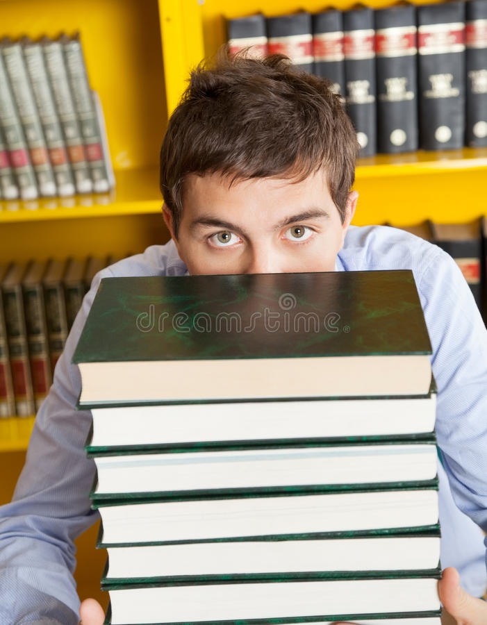 Male Student Peeking Over Stacked Books In Library stock images