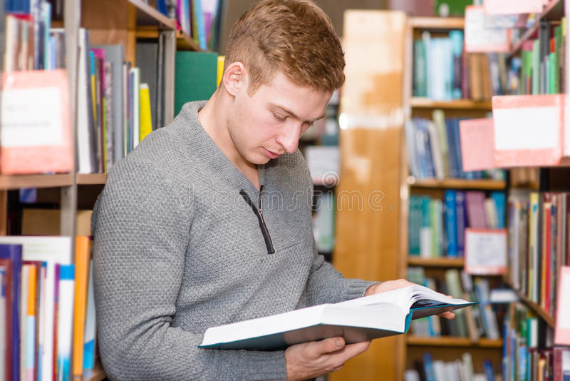 Male student reading book in library royalty free stock photos