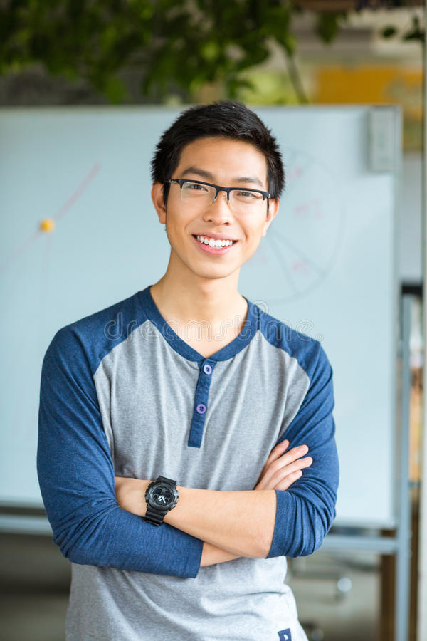 Male student standing with arms folded in university. Portrait of a smiling asian male student standing with arms folded in university and looking at camera stock image