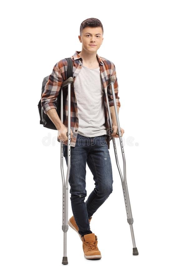 Male student walking with crutches. Full length portrait of a male student walking with crutches isolated on white background stock photos