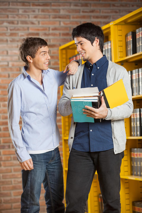 Free Male Student With Books Looking At Friend In Royalty Free Stock Photos - 37123248