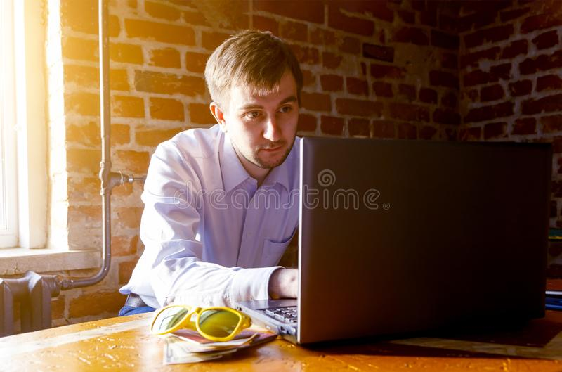 Male student work on computer touch pad , young business man use laptop sitting at wooden table , freelancer working on notebook royalty free stock images