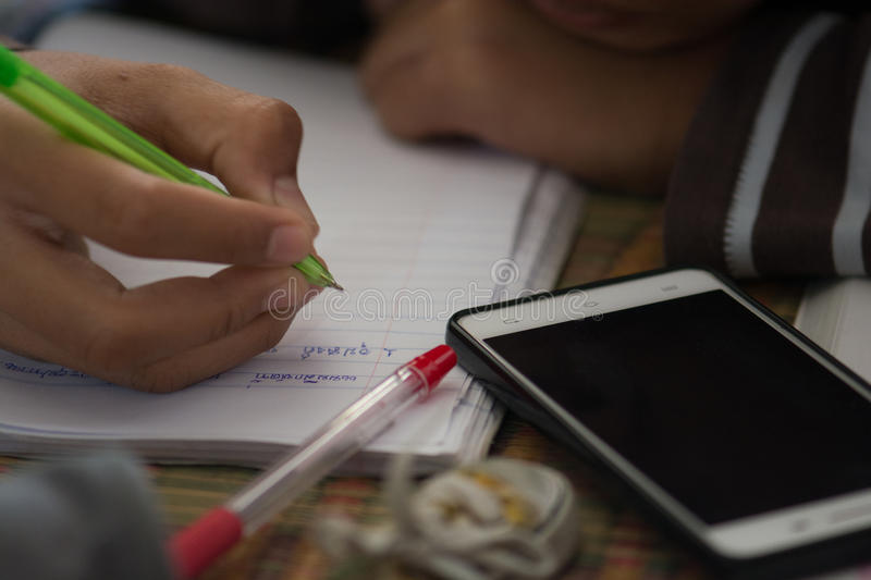 Male students are doing homework with intent. Search the Internet and in phone books. To prepare teachers. stock image