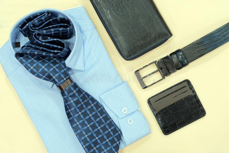 Male style concept. The layout of accessories for men. Blue shirt, tie, belt, wallet and business card holder. Yellow background. stock photography