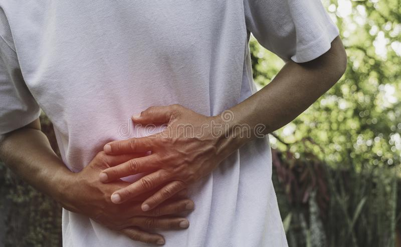 Male suffering from stomachache pain. A man stomachache at outdoor,Healthy concept stock photo