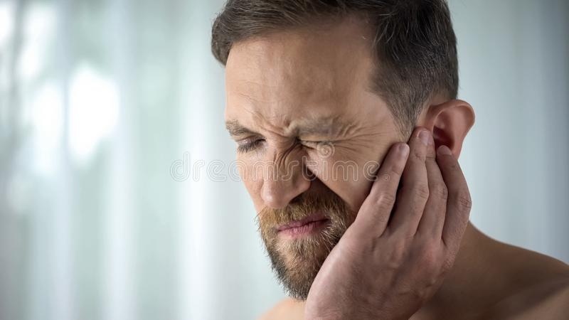 Male suffering from tooth ache, touching cheek, pulp inflammation, gingivitis. Stock photo stock photos