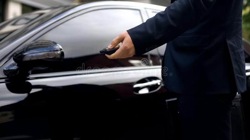 Male in suit pressing remote control of car, alarm system, auto protection stock photography