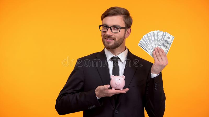 Male in suit showing piggy-bank and dollars, pension fund, retirement income. Stock photo royalty free stock photos