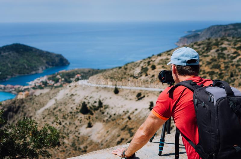 Male summer holiday vacation on Kefalonia Greece. Photographer with backpack enjoying capture of Mediterranean village stock image