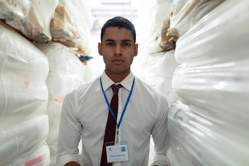 Male supervisor looking at camera in warehouse. Portrait of handsome young Caucasian male supervisor looking at camera in warehouse. This is a freight royalty free stock image