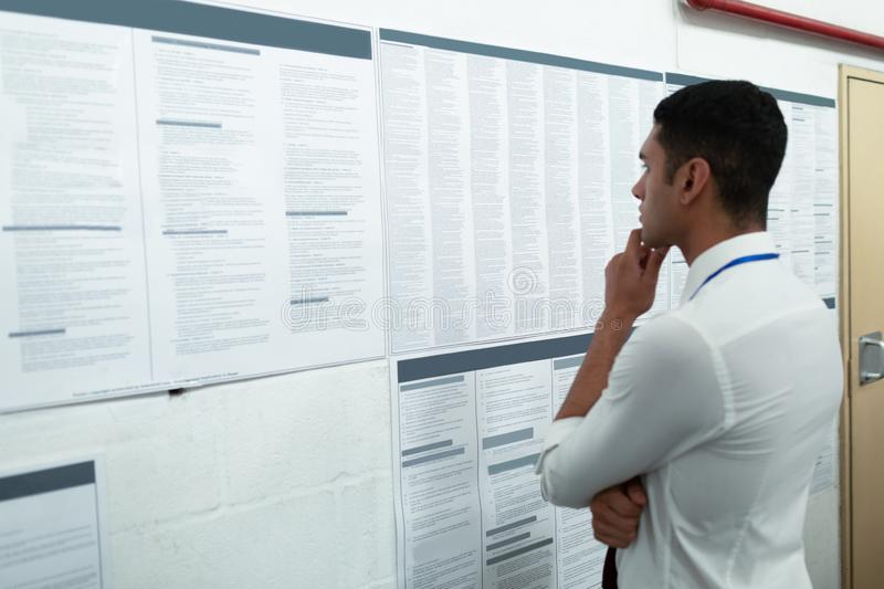 Male supervisor looking at inventory records on wall. Side view of handsome young mixed-race male supervisor looking at inventory records on wall. This is a royalty free stock images